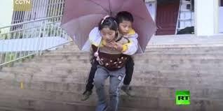 بالفيديو  :في قصة مؤثرة  .. طفلة تحمل شقيقها المعاق على ظهرها إلى المدرسة كل يوم
