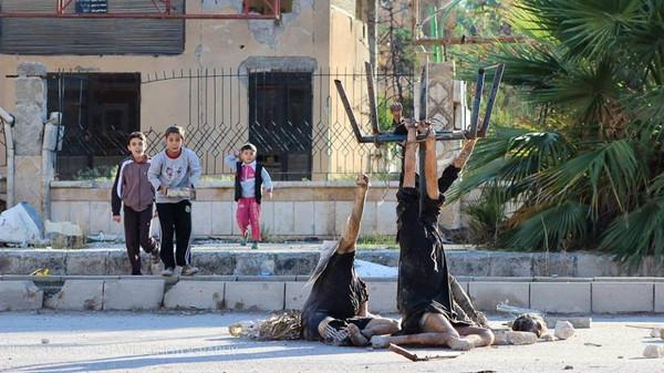 سوريا : أجساد معلقة بالشارع وأطفال يلهون حولها (صورة)