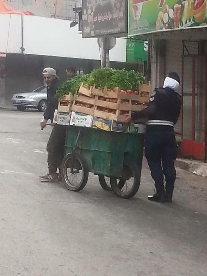 """بالصور ..  اربد : شرطية  تساعد رجل مٌسن  على """"جر"""" عربته"""