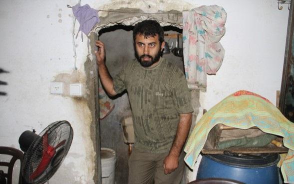 """بالصور : فلسطيني  يعيش في حفرة وقماشة تفصل """"الحمام"""" عن """"المطبخ"""""""