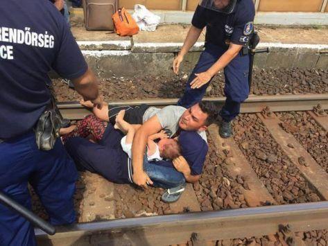 بالفيديو والصور.. مشهد مؤثر للاجئ سوري يلقي زوجته وابنه على سكة قطار