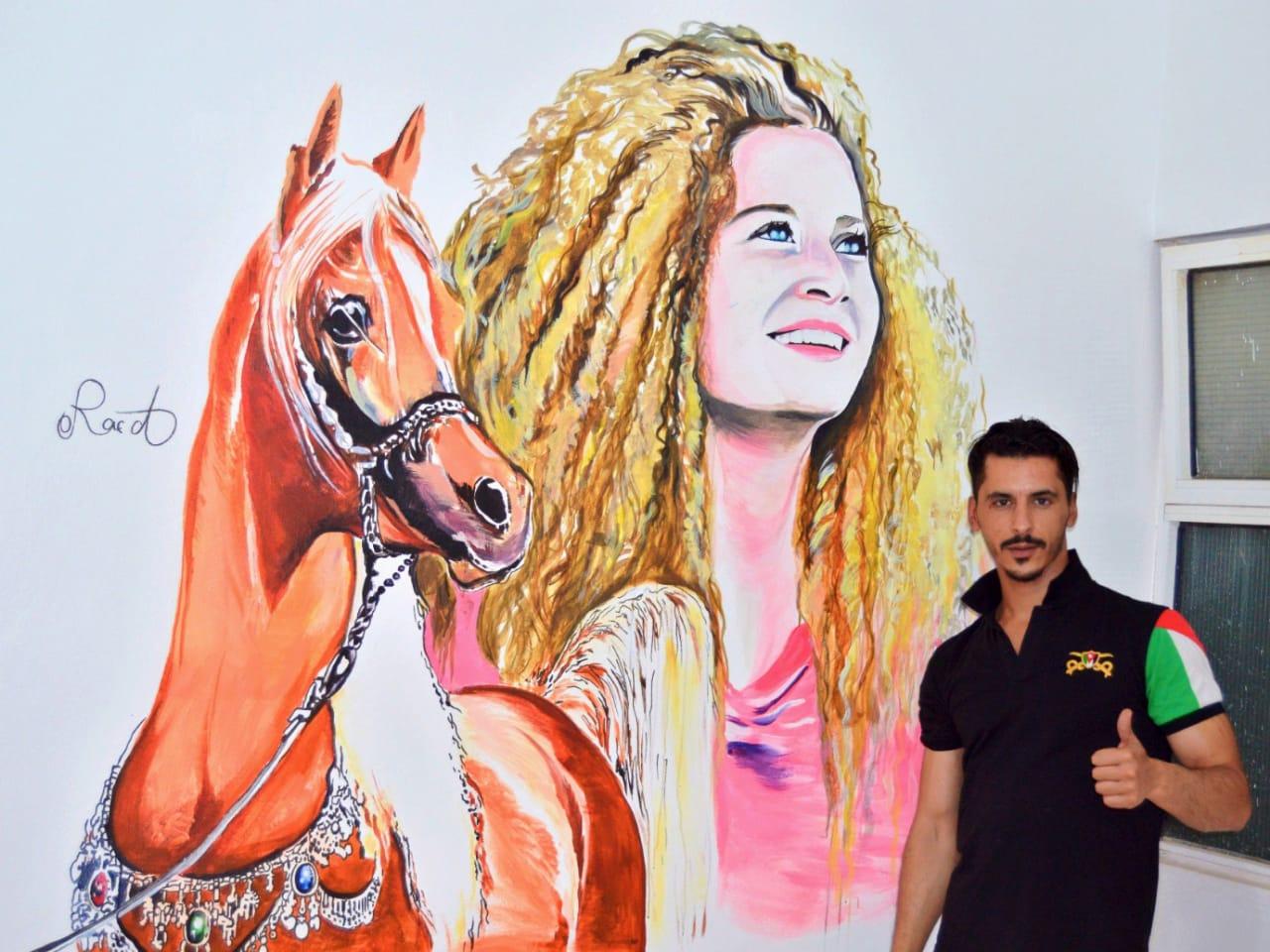 فنان اردني يرسم جدارية لعهد التميمي في الطفيلة