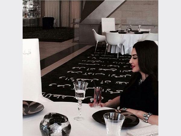 صور ميساء مغريى وهي تجلس في إحدى المطاعم وتظهر خلفها سجادة سوداء مطرزة