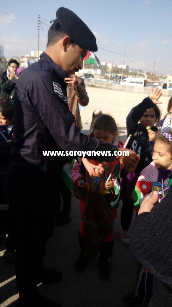 بالصور ..  الامن يقوم بتوزيع العصير والسكاكر على الاطفال المشاركين بالاعتصام امام السفارة الامريكية