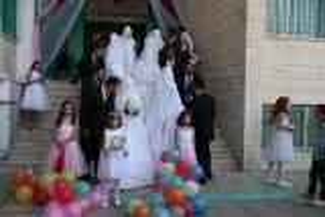 بالصور.. زفاف جماعي بعمان لـ34 عريساً وعروسا