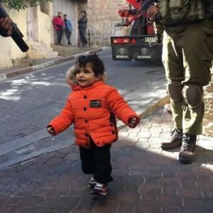 """صور..طفلة فلسطينية في الخليل تثير اهتمام الفيسبوك:""""البراءة تتصدى للبندقية"""""""