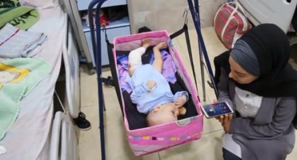 """سيدة فلسطينية تُمارس دورها كـ""""أم بديلة"""" لرضيع غزي حرمه الاحتلال من ذويه"""