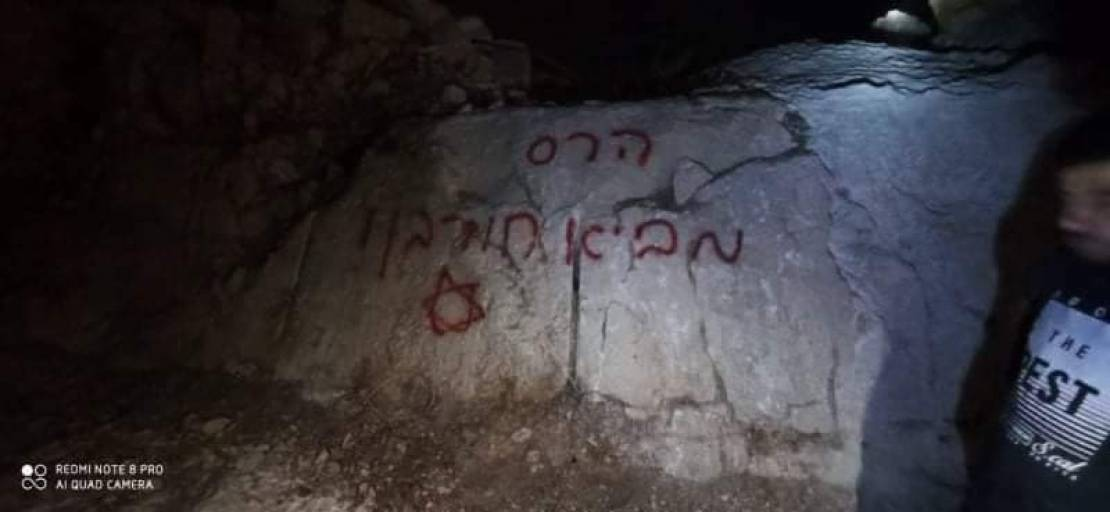 بالصور  ..   مستوطنون يحرقون جرافة ويخطون شعارات عنصرية جنوب نابلس