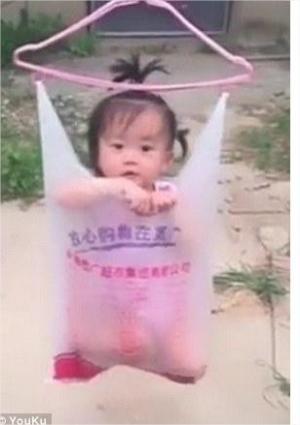 بالفيديو ..  أم تعلق طفلتها بكيس بلاستيك على حبل غسيل