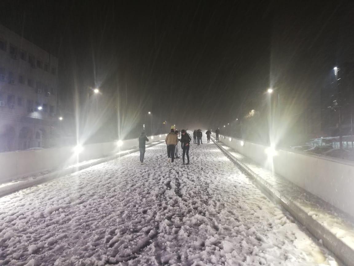 """بالصور  .. """"الباص السريع"""" ساحة للعب في الثلج بعمان"""