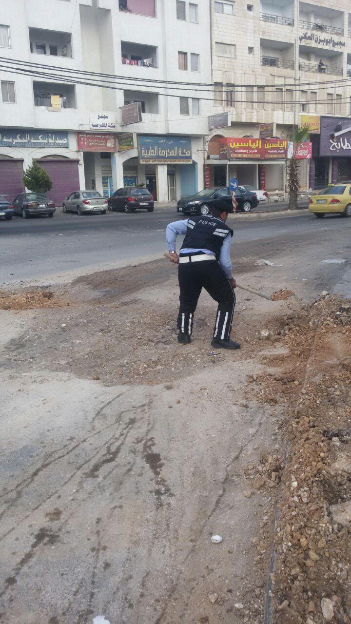 بالصور .. شرطي سير يردم حفرة تركها احد المقاولين مكشوفة بوسط الشارع في اربد