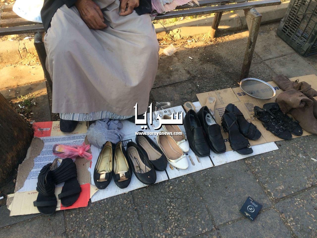 بالصور  ..  عجوز سبعيني على قارعة الطريق في عمان  ..  يبيع أحذية منزله لكي يأكل الطعام و لا أحد يشتري منه